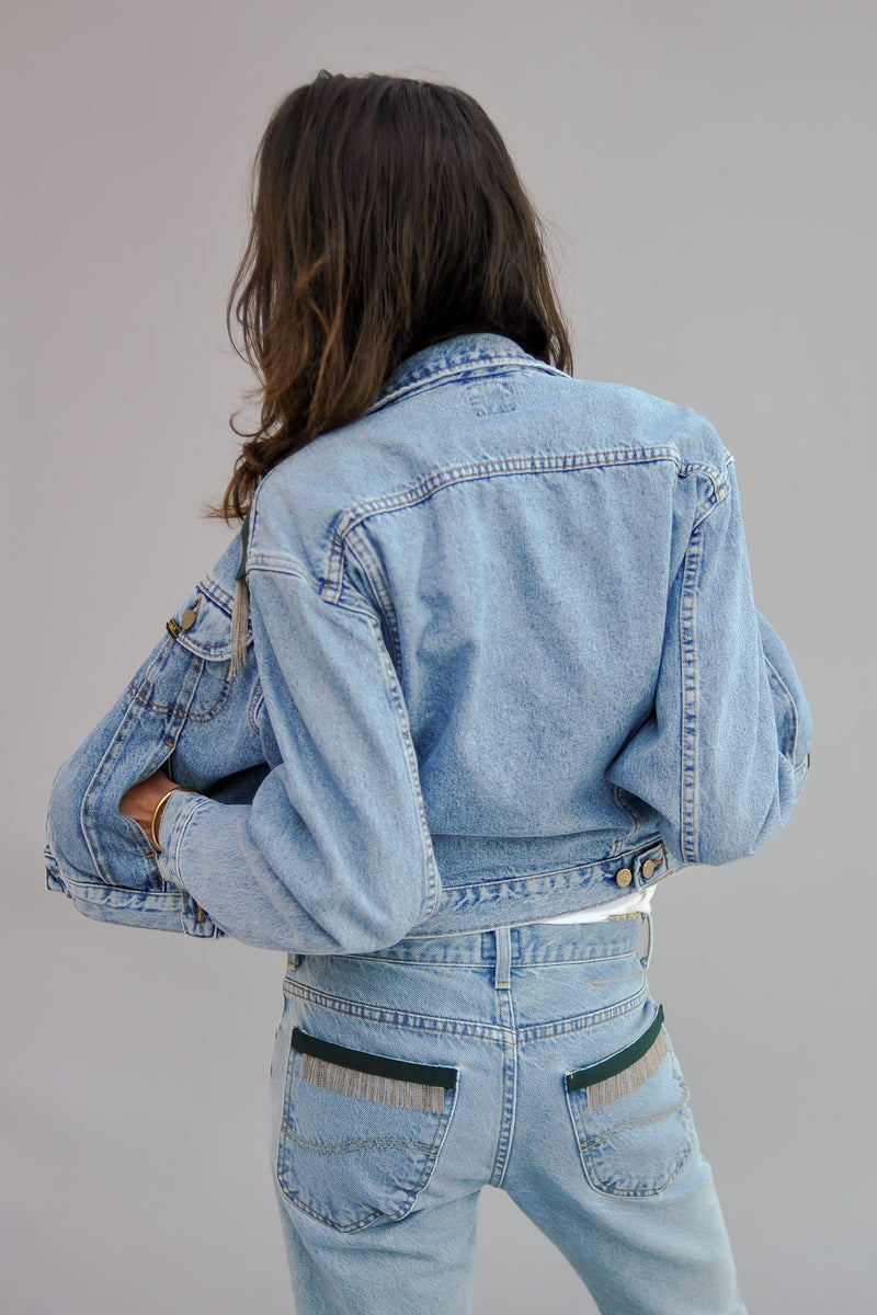 SARAH DE SAINT HUBERT upcycled denim jacket made of cotton with hand embroidered chains and dark green tape applications at the shoulders. Slim fit, slightly cropped and pulls in at the waist giving you a flattering silhouette.