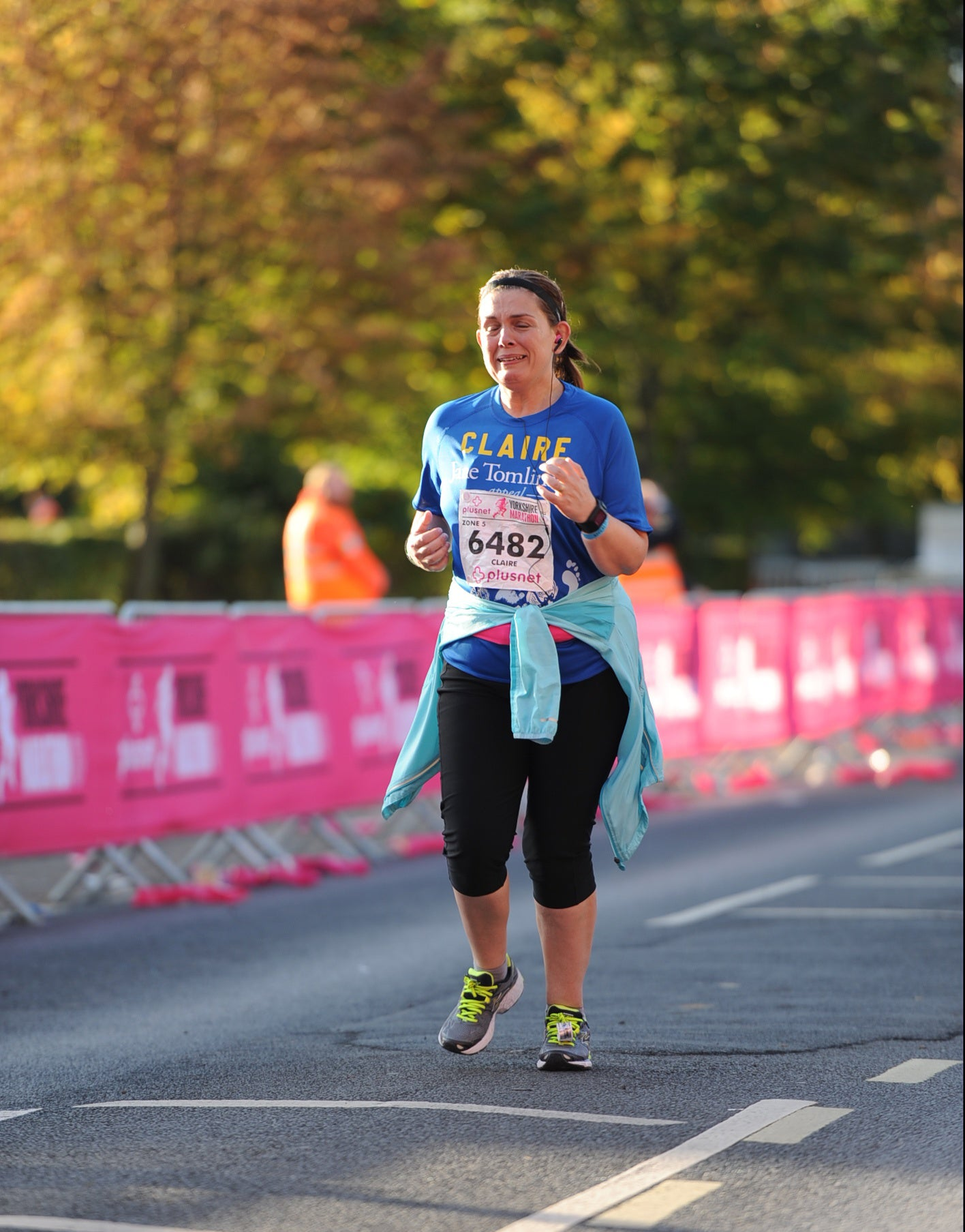 A woman running in the autumn sunshine, with race boards at the side of the road. She is crying.