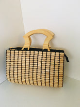 Cream color handcrafted bag made out of beads with wooden handles.