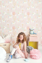 Soft pink background with unicorns, blossoms and trees makes for a whimsical unicorn pink wallpaper design.