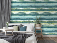 Sunsets and silhouettes make up this blue green wallpaper design with hints of metallic to add to the shine. A good choice for a bedroom, dining room, or hallway.