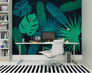 AN array of tropical leaves in bright greens and Turquoise on a dark black background make this Jungle Leaves Wallpaper a striking choice for a home office, study or lounge.