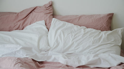 Pink and White Pillows on a bed