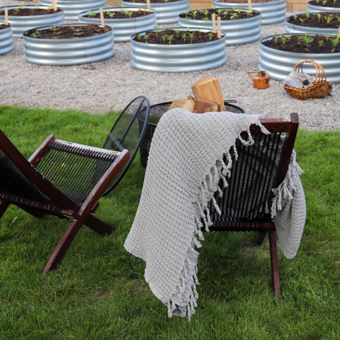 2 chairs in front of a fire pit with a waffle blanket hanging off of it