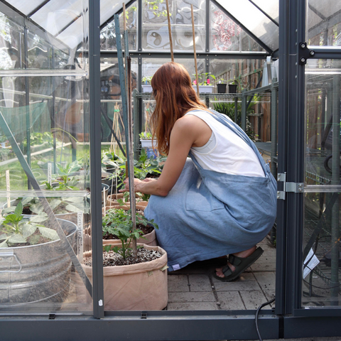 A woman planting herbs in her backyard in a greenhouse