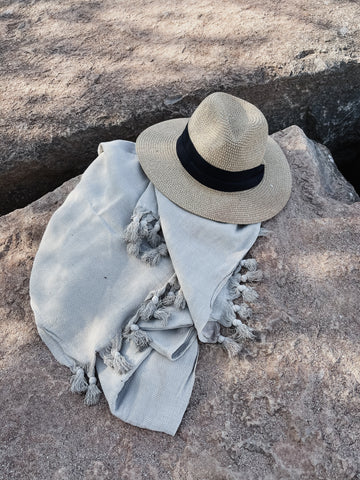 A Turkish Towel and a beach hat on a rock