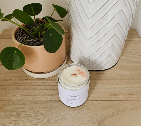Natural Soy Candle on a light wood nightstand beside a plant and lamp