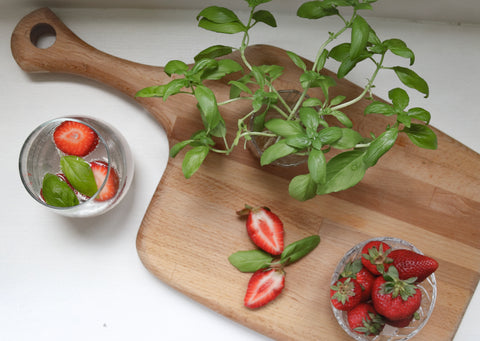 Ingredients basil and strawberries on a cutting board