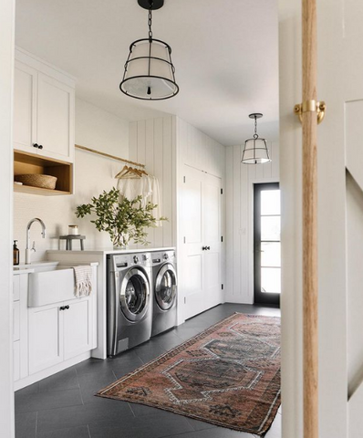 Beautiful large laundry room with plants, rug, and sink