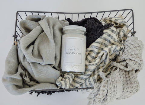 Jar of Lavender Laundry Soap laying on a pile of textiles in laundry basket.