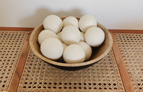 Bowl of Wool Dryer Balls on a wooden indoor bench