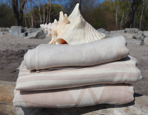Turkish Towels folded up on a log at a beach with a sea shell on top