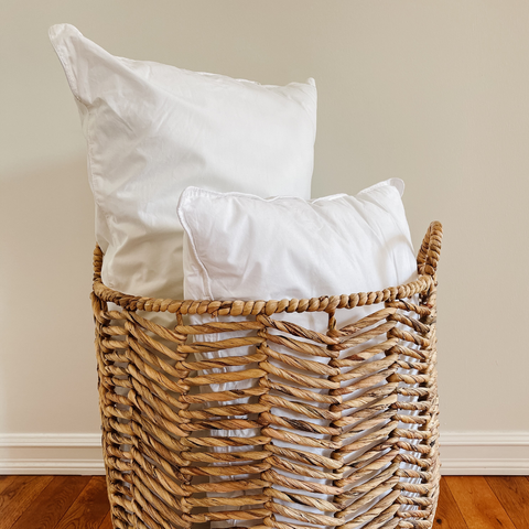 Two sleep pillows with no case in a basket