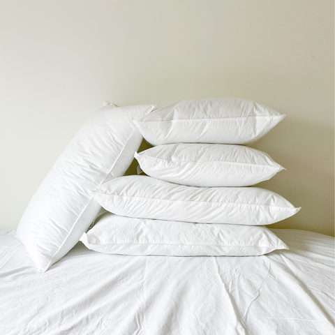 A stack of sleep pillows with no cases on top of each other on a bed
