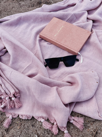 Sunglasses on a pink turkish towel on the beach