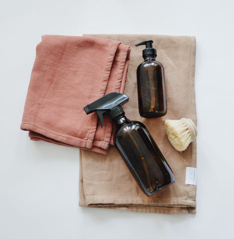 Two spray bottles and cleaning brush on top of two towels