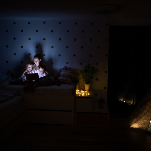 A parent and child in a dark bedroom