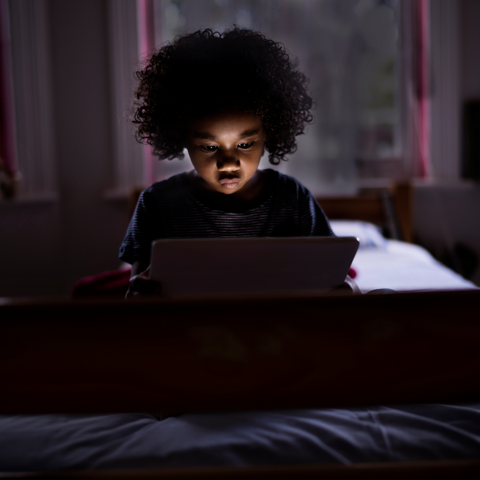 Little girl watching something on the Ipad in her bed