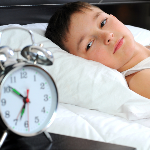 Little boy looking at a clock in bed