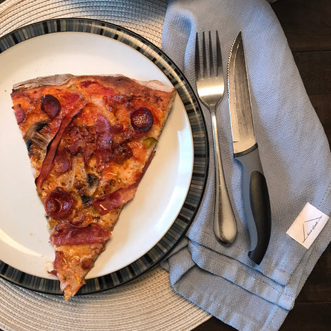 Slice of pizza on a plate with fork and knife and House of Jude Cloth Napkin