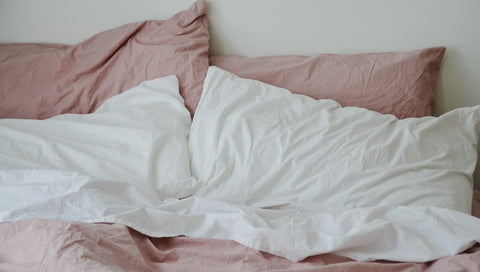 A bed with pink and white Turkish Cotton bedding
