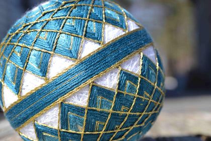 Japanese temari embroidered in teal and gold in kiku pattern