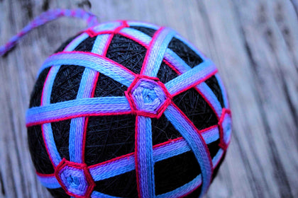 Japanese temari ball wrapped in black and embroidered in red and purple threads