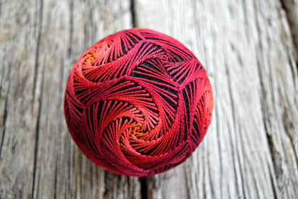 Japanese temari ball embroidered in swirl pattern in reds and oranges