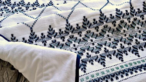 Blue and white hand embroidered blanket in geometric bands