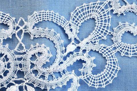 Closeup of handmade vologda lace necklace on light blue background