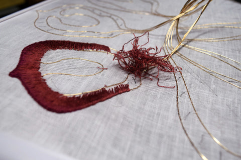 Tearing out progress on a stumpwork petal with knot of threads