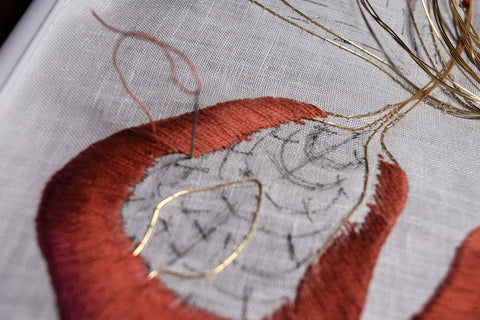 Closeup of embroidered iris petal showing shading from russet to dark peach