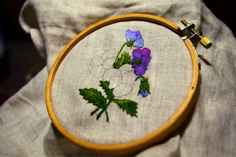 Purple pansy embroidered design unfinished in hoop - leaves and small flowers complete