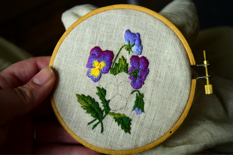 Design of purple and yellow pansies against green leaves, one flower incomplete in hoop.