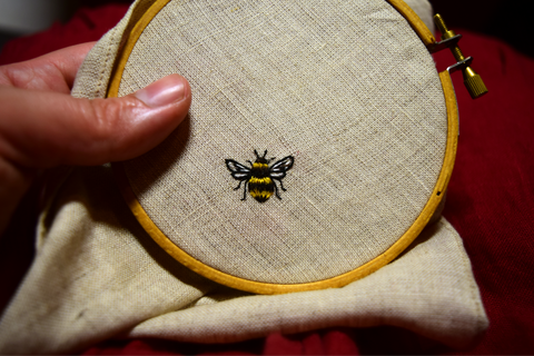 Tiny bee hand embroidered on oatmeal linen in yellow and black