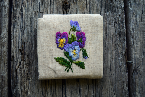 Back of business card case hand embroidered with blue and purple pansies