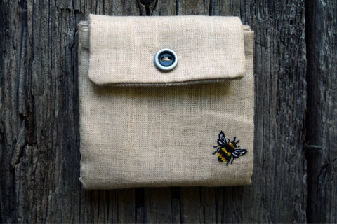 Front of business card case with button snap and embroidered bee in corner
