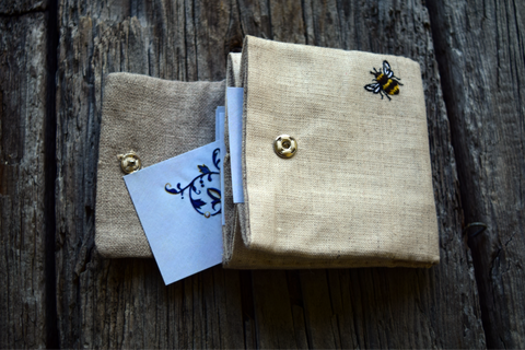 Open business card case with cards, showing embroidered bee