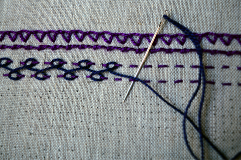 Embroidered bands in purple with navy blue interlacing threads