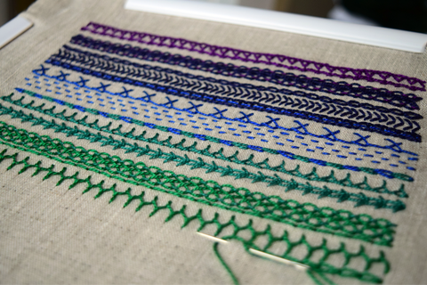 Embroidered band sampler with lines of stitches in shades from purple to deep green