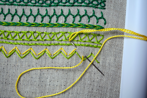Embroidery band sampler in greens and yellows with arrowhead stitch in progress
