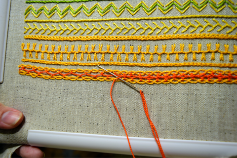 Embroidery band sampler in yellow and orange with interlaced cable chain stitch in progress