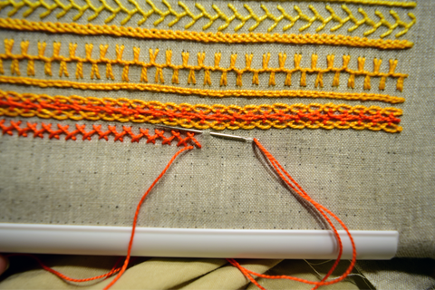 Embroidery band sampler in yellow and orange with herringbone stitch in progress
