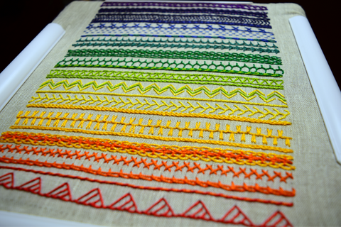Embroidery band sampler almost complete in bright rainbow colors