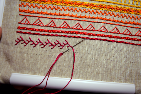 Hand embroidered band sampler in progress showing double feather stitch in red thread