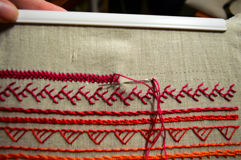 Hand embroidery band sampler in progress showing closed herringbone stitch in red thread