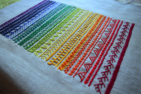 Hand embroidered band sampler in rainbow colors showing a variety of line stitches