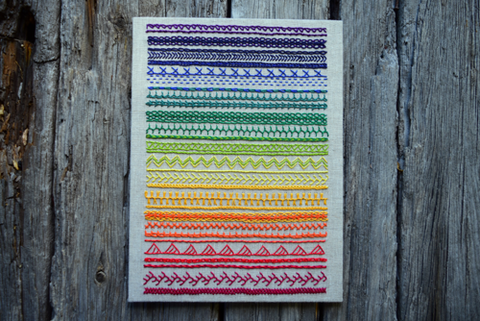 Finished band sampler in rainbow colors on oatmeal linen, simply mounted and set against wood backround