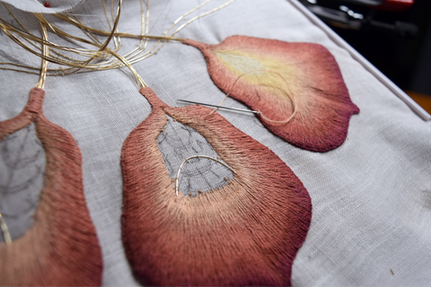 Three iris petals; one finished and two nearing completion. All in shades of rust and peach.