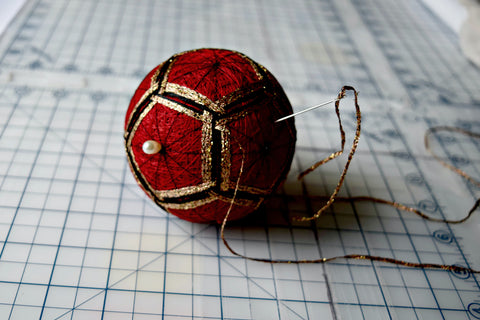 Red and gold temari ball in the making